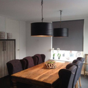 Een robuuste hanglamp boven de eettafel\'